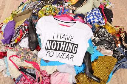 Big pile of clothes thrown on the ground with a t-shirt saying nothing to wear. Close up on a untidy cluttered wardrobe with colorful clothes and accessories, many clothes and nothing to wear.